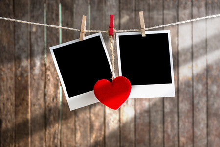 Two blank instant photos hanging on the clothesline with  red heart,.Clipping path for insert Photo