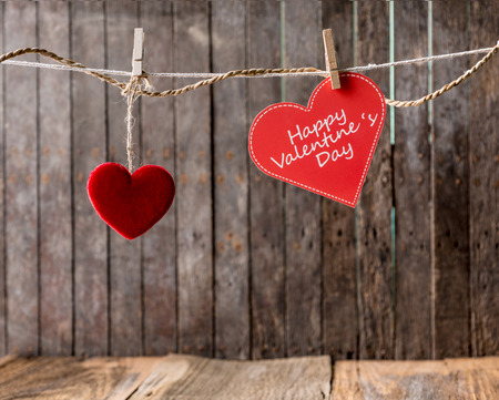Red hearts with clothespin hanging on clothesline ,Wooden background photo