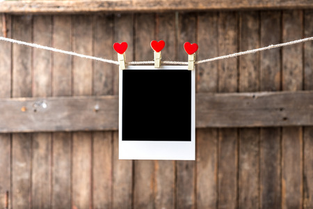 Old picture frame hanging on the clothesline,Selective focus,Clipping path for insert Photo photo