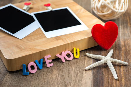 wooden insert: Two blank instant photos with red hearts.On wooden background,Clipping path for insert Photo Stock Photo