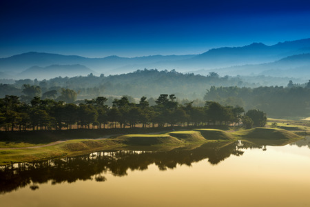 golf course at dawn backlit by rising sun photo
