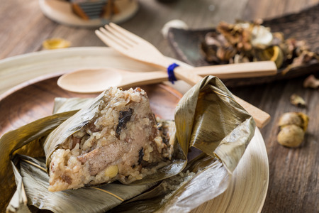 Asian Chinese rice dumplings or zongzi with tea on wooden background