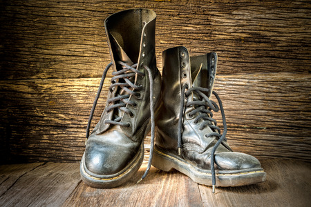 foot ware: Pair of old worn leather boots on wooden floor boards