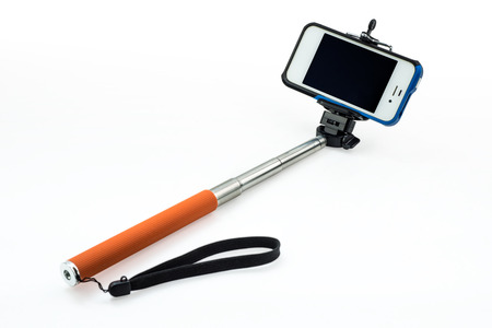 an extensible selfie stick with an adjustable clamp on the end on a white background Archivio Fotografico