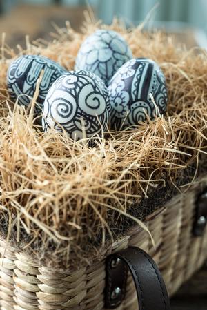 studio shot: Doodles painted easter eggs in brown basket,studio shot