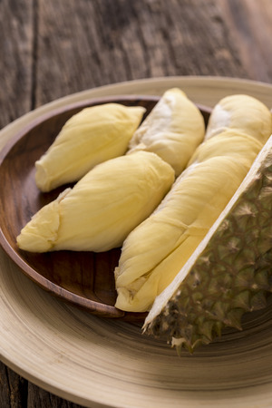 Close up of  yellow Durian in wooden plate on wood table