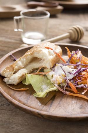 hotdog: piece of Hotdog remains on wooden plate, food scraps