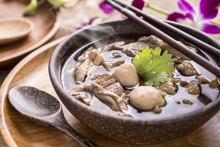 Close up of a bowl of Chinese style beef noodle soup on wooden background. Selective Focus
