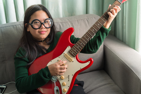 gig: Happy smiling girl ,wearing glasses,learning to play the Electric guitar at home laying on sofa