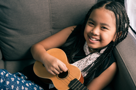 Happy smiling girl,dreadlocks hair style ,learning to play the Ukulele