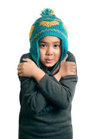 暖かい帽子、白で隔離の愛らしい幸せな子冷たい少女の肖像画