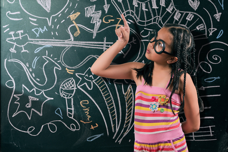 Portrait of cute girl in eyeglasses looking at camera by the blackboard with chalk drawings of musical instruments. 스톡 콘텐츠