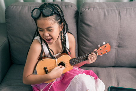melodies: Happy smiling girl,wearing glasses,dreadlocks hair style ,learning to play music