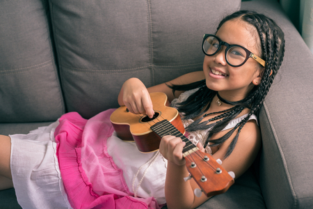 cool gadget: Cute little girl,wearing glasses,dreadlocks hair style ,playing with guitar at home laying on sofa