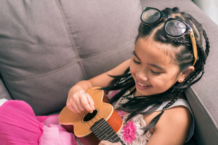 acoustic ukulele: Happy smiling girl,wearing glasses,dreadlocks hair style ,learning to play music