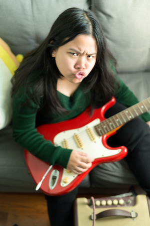 amp: Happy cheeky girl,learning to play the Electric guitar at home laying on sofa
