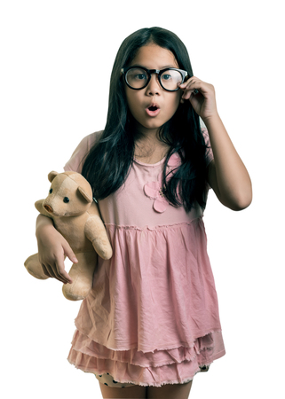 longhaired: Cute girl  Wearing Eyeglasses, holding her dollm Showing Oops Expression at the Camera ,isolated on white, This has clipping path. Stock Photo