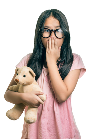 dismay: Cute girl  Wearing Eyeglasses, holding her dollm Showing Oops Expression at the Camera  isolated over white with clipping path Stock Photo
