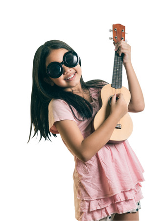 portrait of young girl wearing glasses with a Ukulele,isolated on white, This has clipping path. Фото со стока