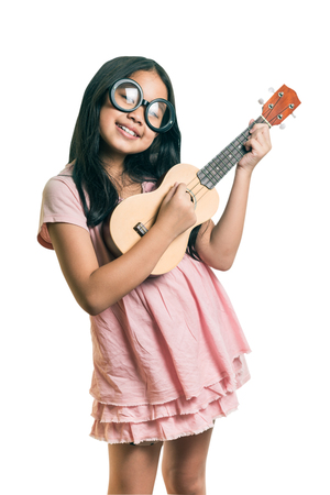 portrait of young girl wearing glasses with a Ukulele,isolated on white, This has clipping path. Zdjęcie Seryjne