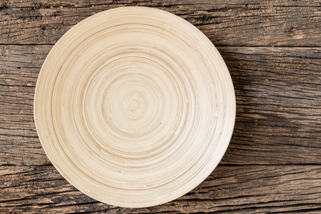 The brown wooden plate on a rustic table closeup.  Top View with Copy Space for Text, wooden background. 免版税图像