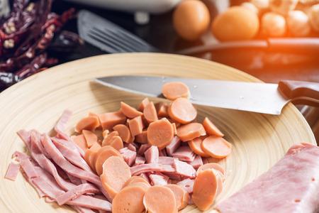 pancetta cubetti: Tritate il prosciutto e salsiccia sul blocchetto di spezzettamento con coltello Archivio Fotografico