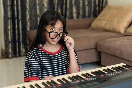 making music: Portrait of the Cute silly young girl making funny faces, studding to play piano, looking at camera,Soft focus shot Stock Photo