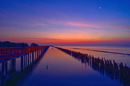 Fishermen leave fishing while the twilight is on and the crescent moon still shines at wooden red bridge over the sea. Gulf of Thailand, near by Tha Chin estuary, Samutsakhon province, Thailand
