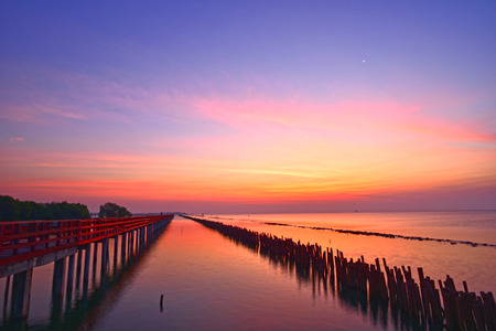 crescent moon and wonderful light at golden hour before sunrise with colorful reflection at red bridge near by Tha Chin estuary, Gulf of Thailand, Samut Sakhon province, Thailand.