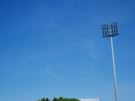 Sports light pole or Stadium Light tower in sport arena on blue sky with clouds and copy space.