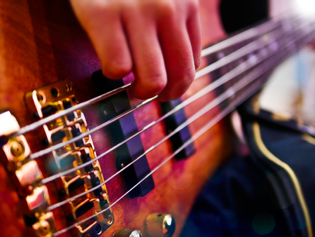 Closeup of hand playing bass guitar during a performance. 写真素材