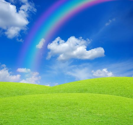 Green field on blue sky with rainbow photo
