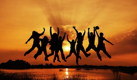 Image of silhouettes group jumping with sunset background Stock Photo