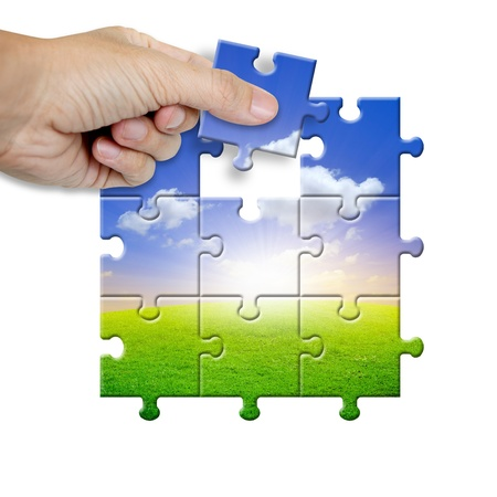 problems solutions: Hand collecting a part of a landscape puzzle  Stock Photo