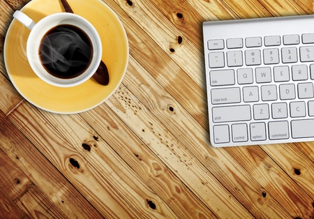 computer keyboard and a cub of coffee on wood table photo