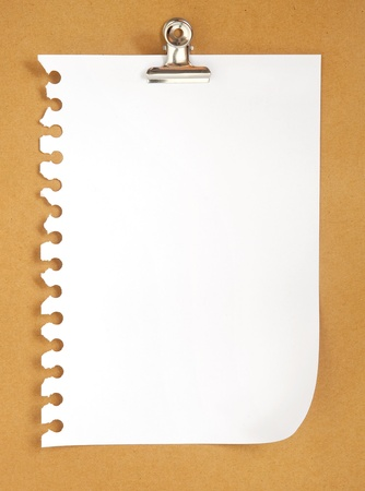 blank note paper on cardboard background with clip  photo