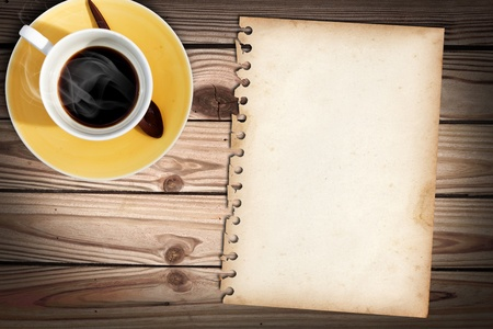 Old note paper on wood table with a cub of coffee photo