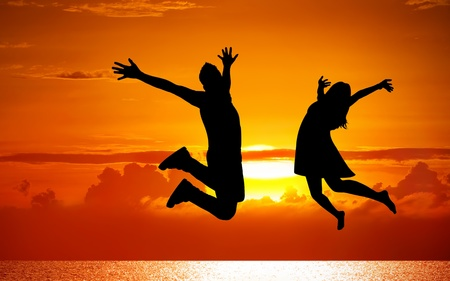 Silhouettes of couple jumping on sunset background  photo