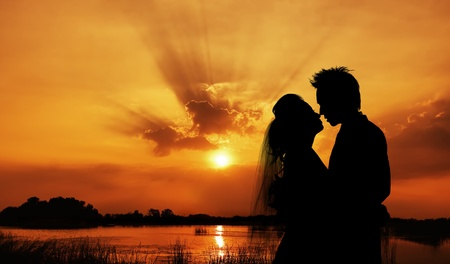 silhouette of a young bride and groom on Sunset background Stock Photo