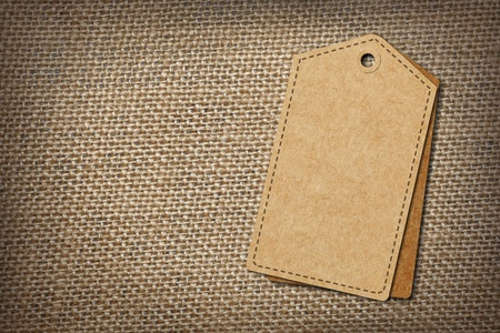 background of burlap hessian sacking with blank paper tag