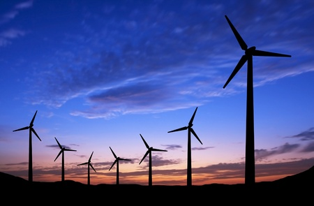 Silhouette of windmills on sunset background with space