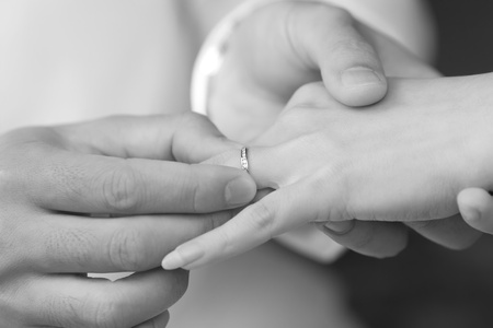 put: groom put an engagement ring on bride finger Stock Photo