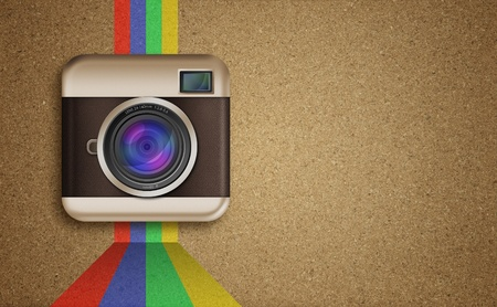 retro camera icon with rainbow colors on corkboard background photo