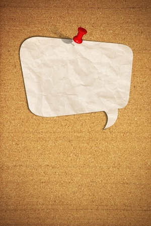blank speech bubble note paper with push pin on cork board photo