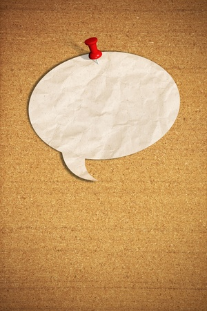 blank speech bubble note paper with push pins on cork board photo