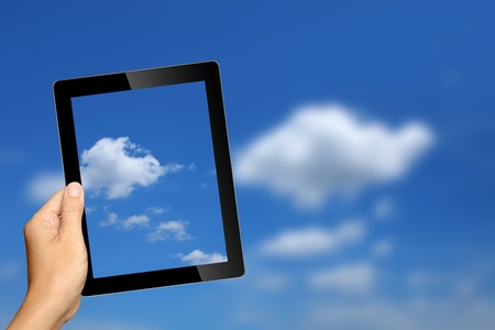 capture: hand holding tablet pc with cloud background