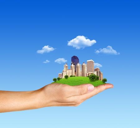 Concepto humano mano que sostiene una ciudad en la hierba verde