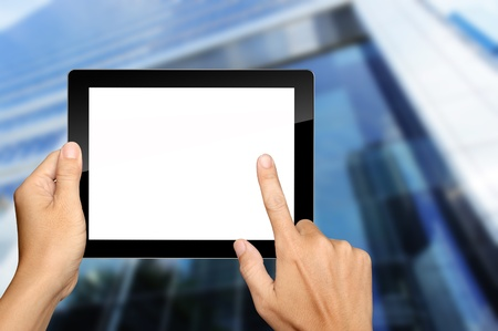 Hands are holding and pressing on Tablet PC with building background