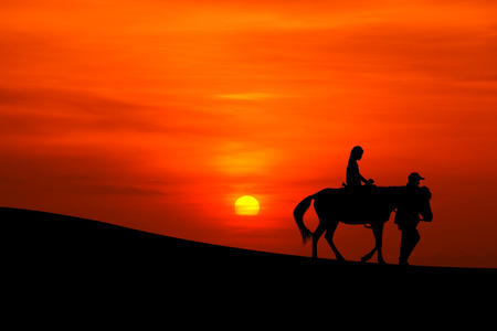 sillhouette: sillhouette of a journey on horseback  with sunset Stock Photo