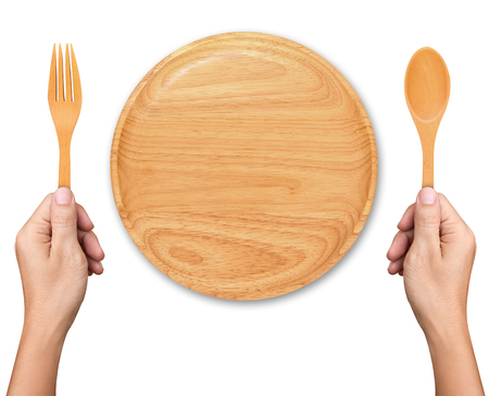 Hands hold spoon and fork with Empty wood plate on white background